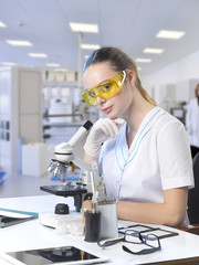Portrait of a young beautiful girl doctor assistant assistant in protective yellow glasses at her workplace with a microscope.