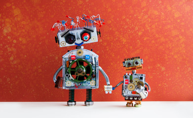Family robots. Big robot mom holds the hand of a small child robot. Creative design futuristic cyborg toys on red wall background.