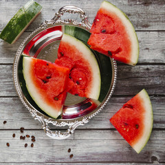Overhead view of watermelon slices with bowl on wooden table