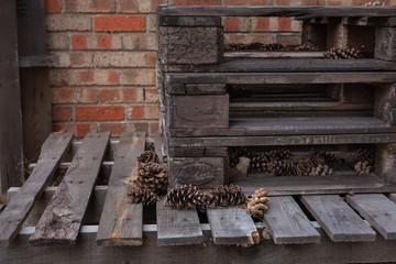 Pile of palettes in front of brick wall with pine cones