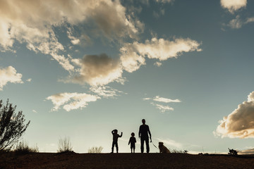 Family with dog standing in the field against cloudy sky during sunset