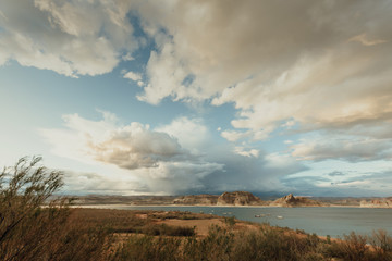Tranquil view of Lake Powell by mountains against cloudy sky