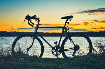 Active sunrise at the lake. Bike in a beautiful colorful scenery.