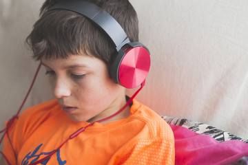 Close-up of boy listening to music using headphones on sofa at home