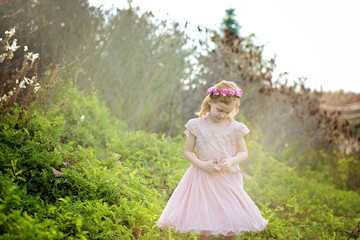 Carefree girl wearing wreath while standing amidst plants on field at park