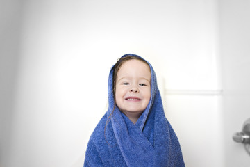Close-up portrait of girl wrapped in towel standing in bathroom