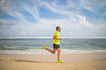 Jogging on a tropical sandy beach near sea / ocean.