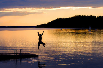Silhouette of young man jumping from a pontoon into lake at sunset