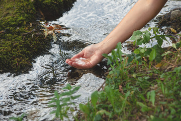 woman hand with water from a pure mountain stream
