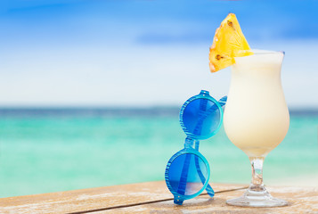 glass of delicious cold pina colada cocktail by the beach