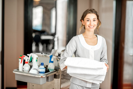 Portrait of a young woman chambermaid holding a towel standing with maid cart full of cleaning stuff in the hotel corridor