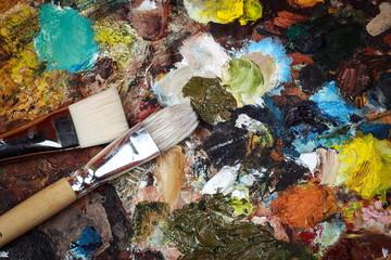 Макрофотография палитры искусства с красочными смешанными красками и щетками