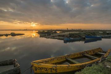 Amanecer en la bahía y barco en el Delta del Ebro