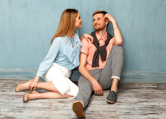 .Fashion girl and guy in outlet clothes posing on a blue background