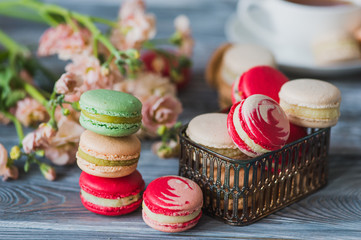 Macarons on rustic wood table, French candy meringue-based made with egg white, icing sugar, granulated sugar, almond powder or ground almond and food coloring