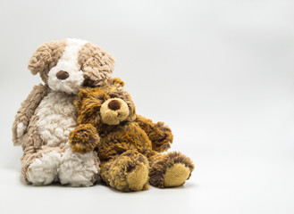 2 cuddly plush toy teddy bears leaning against one another isolated on a solid background with copy space