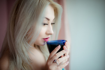 blue-eyed blonde in a home dressing-gown near a window with a blue cup