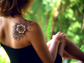 Henna tattoo design on shoulder back. Beautiful indian ornaments painted on a body part.