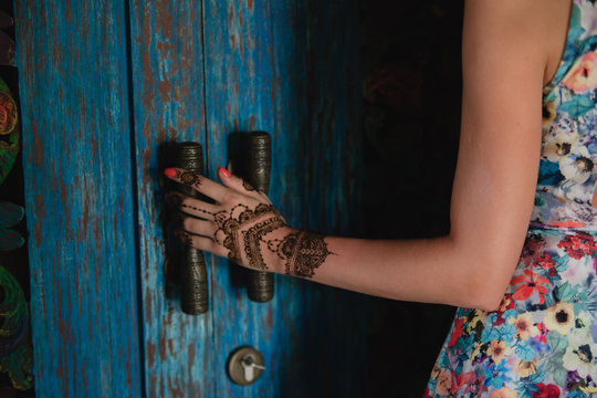 Female hand with henna tattoo touching antique blue door. Beautiful indian mehendi ornaments painted on a body part.