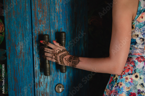 88b271880 Female hand with henna tattoo touching antique blue door. Beautiful indian  mehendi ornaments painted on