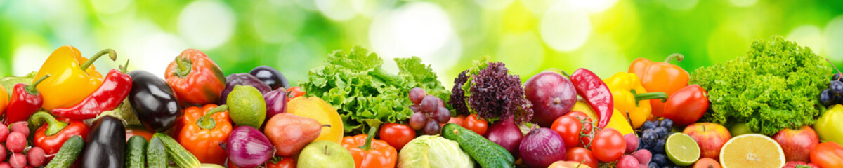 Aluminium Prints Vegetables Panorama of fresh vegetables and fruits on blurred background of green leaves.