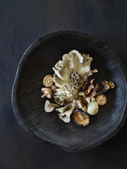 Wooden bowl of various mushrooms
