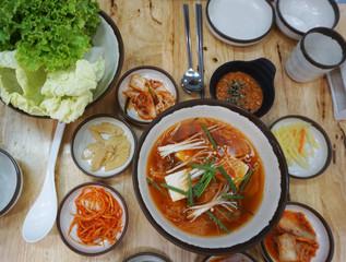 Top view of Korea kimji soup with soft tofu and enoki mushroom. Korea cuisine, hot soup serve with pickle vegetable side dish.