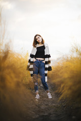 Young beautiful girl in the field. She wears a sweater and jeans. Yellow background.