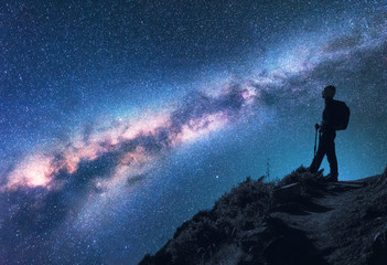Space with Milky Way. Silhouette of a woman with backpack at night. Girl on the mountain peak and starry sky. Sky with stars and woman. Trekking. Night landscape with bright milky way and traveler