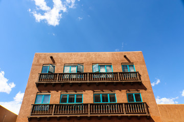 Santa Fe adobe Building with balconies and turquoise windows against a blue sky with clouds