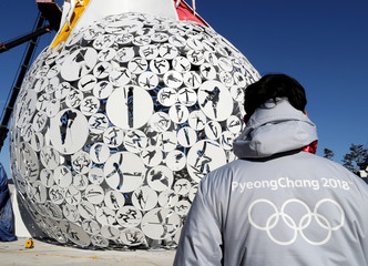 A volunteer stands at the base of the Olympic Cauldron for the upcoming 2018 Pyeongchang Winter Olympic Games at the Alpensia resort in Pyeongchang