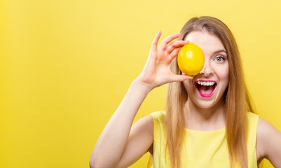 Happy young woman holding a lemon on a yellow background