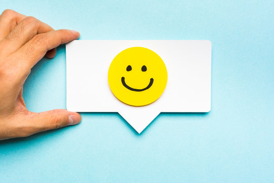 Happy face smiling comment on speech bubble and blue background.