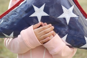 Small Hands Holding Folded American Flag 1