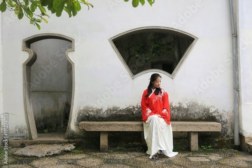 A Young Woman In Red Chinese Costume Sitting Traditional Patio Front