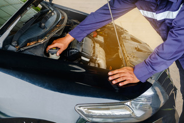 Man in blue safety uniform checking car engine before the trip for vehicle and transportation concept