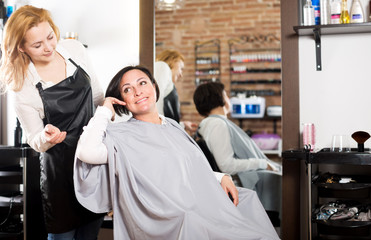 Woman consults with a young hairdresser