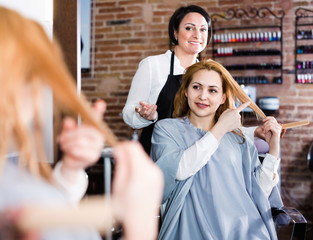 Woman points to master in hairdress salon right hair length for haircut