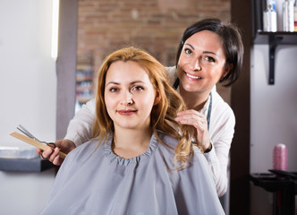 Woman very much likes her fashionable hairdress in hairdressing salon