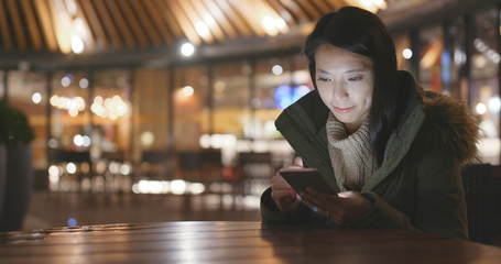 Woman using smart phone outside restaurant at night