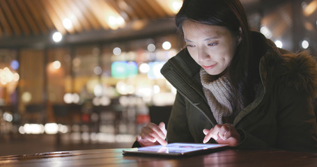 Woman using cellphone in outdoor cafe at night