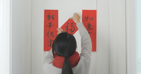 Woman sticking chinese calligraphy on the door for lunar new year