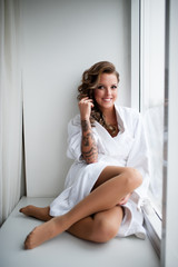 Beautiful woman with a tattoo in a white coat smiles at the hotel.
