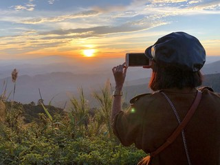 woman take picture of sunset hill