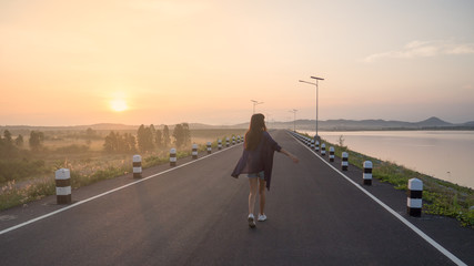 Young asian woman walking on the road at sunrise