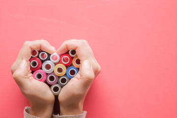 Colorful spools of threads in hands heart shape on the pastel pink background. Womanly hobby. Sewing concept. Empty place for text.