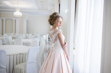 A beautiful woman in a pink wedding dress in a big festive hall