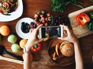 Woman hand holding smart phone for taking a photo food on table.