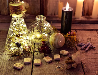 Magic bottles with lights, runes and black candle on witch table. Occult, esoteric, divination and wicca concept. Halloween background with vintage objects
