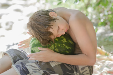 Boy holding large watermelon on his knees on summer beach